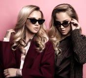 Moderne zwei blonde Frauen im Mantel mit Sonnenbrille Modeherbst-Winterfoto stockfotos