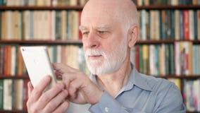 Moderner älterer Mann zu Hause unter Verwendung des Mobiltelefons, grasend und lesen Bücherschrankbücherregale im Hintergrund stock footage