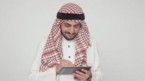 Moderner Araber im Büro Ein Mann im Nationalkostüm lächelt und druckt auf einer digitalen Tablette In den Händen von den arabisch stock footage