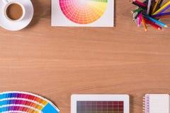 Moderner Büroarbeitsplatz mit digitaler Tablette, Notizblock, bunten Bleistiften, Tasse Kaffee und Farbmustern auf einem Desktop Lizenzfreies Stockfoto