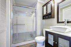 Moderner Badezimmerinnenraum mit braunen Kabinetten Stockfoto