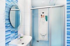 Moderner blauer Badezimmerinnenraum mit rundem Spiegel Stockfotos