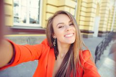 Moderner Blick, heißes Tagesmodell einer jungen Frau, die selfie, eine rote Jacke, blondes Haar über dem Stadt warmen backgr drau Stockfotografie