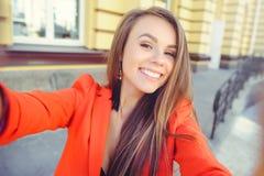 Moderner Blick, heißes Tagesmodell einer jungen Frau, die selfie, eine rote Jacke, blondes Haar über dem Stadt warmen backgr drau Lizenzfreies Stockfoto