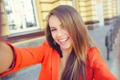 Moderner Blick, heißes Tagesmodell einer jungen Frau, die selfie, eine rote Jacke, blondes Haar über dem Stadt warmen backgr drau Lizenzfreies Stockbild