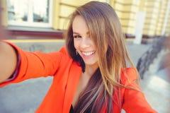 Moderner Blick, heißes Tagesmodell einer jungen Frau, die selfie, eine rote Jacke, blondes Haar über dem Stadt warmen backgr drau Stockfotos