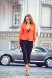 Moderner Blick, heißes Tagesmodell einer jungen Frau, die in die Stadt, eine rote Jacke und schwarzen Hosen draußen tragend, blon Stockfotos