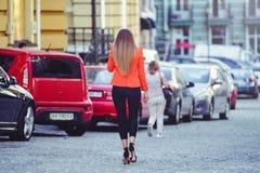 Moderner Blick, heißes Tagesmodell einer jungen Frau, die in die Stadt, eine rote Jacke und schwarzen Hosen draußen tragend, blon Lizenzfreie Stockfotos