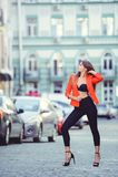 Moderner Blick, heißes Tagesmodell einer jungen Frau, die in die Stadt, eine rote Jacke und schwarzen Hosen draußen tragend, blon Lizenzfreie Stockbilder