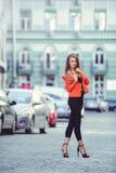 Moderner Blick, heißes Tagesmodell einer jungen Frau, die in die Stadt, eine rote Jacke und schwarzen Hosen draußen tragend, blon Lizenzfreie Stockfotografie