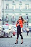 Moderner Blick, heißes Tagesmodell einer jungen Frau, die in die Stadt, eine rote Jacke und schwarzen Hosen draußen tragend, blon Stockbilder