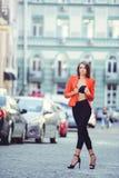 Moderner Blick, heißes Tagesmodell einer jungen Frau, die in die Stadt, eine rote Jacke und schwarzen Hosen draußen tragend, blon Stockfoto
