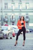 Moderner Blick, heißes Tagesmodell einer jungen Frau, die in die Stadt, eine rote Jacke und schwarzen Hosen draußen tragend, blon Stockfotografie