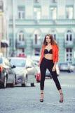 Moderner Blick, heißes Tagesmodell einer jungen Frau, die in die Stadt, eine rote Jacke und schwarzen Hosen draußen tragend, blon Lizenzfreies Stockfoto