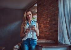 Moderner blonder weiblicher Blogger, der eine Tablette bei der Stellung auf einer Tabelle gegen eine Backsteinmauer in einem Stud Stockfoto