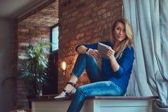 Moderner blonder weiblicher Blogger hält eine Tablette beim Sitzen auf einer Tabelle gegen eine Backsteinmauer in einem Studio mi Stockbilder