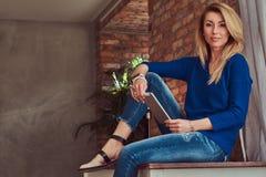 Moderner blonder weiblicher Blogger hält eine Tablette beim Sitzen auf einer Tabelle gegen eine Backsteinmauer in einem Studio mi Lizenzfreie Stockbilder