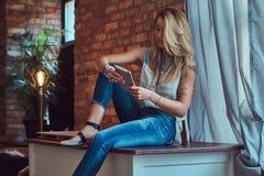 Moderner blonder weiblicher Blogger hält eine Tablette beim Sitzen auf einer Tabelle gegen eine Backsteinmauer in einem Studio mi Lizenzfreies Stockbild