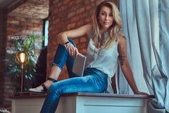 Moderner blonder weiblicher Blogger hält eine Tablette beim Sitzen auf einer Tabelle gegen eine Backsteinmauer in einem Studio mi Lizenzfreie Stockfotografie
