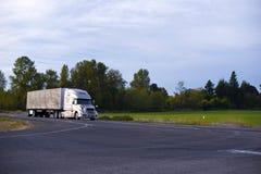 Moderner der Fernstrecke LKW-Planenanhänger halb auf gerader Landstraße Lizenzfreie Stockfotos