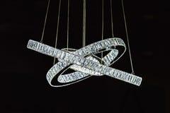 Moderner Designerleuchter in Form von den Ringen verziert mit Glaskristalldiamanten, Leuchterisolat auf schwarzem backgroun Stockfotos