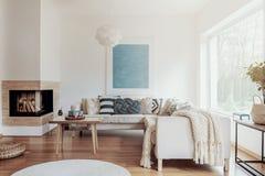 Moderner Eckkamin in einem sonnigen, ruhigen Wohnzimmerinnenraum mit weißen Wänden und in gemütlichen Kissen und in Decken auf ei stockfoto