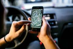 Moderner Fahrer, der on-line-Karten und GPS-Anwendungen mit Smartphone verwendet lizenzfreie stockfotos