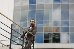 Moderner Geschäftsmann Überzeugter junger Mann in der vollen Klage, die bei mit Stadtbild in draußen stehen weg schaut Lizenzfreie Stockfotografie