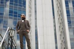 Moderner Geschäftsmann Überzeugter junger Mann in der vollen Klage, die bei mit Stadtbild in draußen stehen weg schaut Stockbild