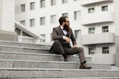 Moderner Geschäftsmann Überzeugter junger Mann in der vollen Klage, die bei mit Stadtbild in draußen stehen weg schaut Lizenzfreies Stockbild