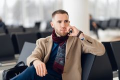 Moderner Gesch?ftsmann des h?bschen Hippies mit Bart um Handy am Flughafen oder am B?rogeb?ude ersuchend stockfotografie