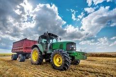 Moderner grüner Traktor auf dem landwirtschaftlichen Feld Lizenzfreie Stockbilder