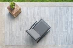 Moderner grauer Lederstuhl mit Vase der Anlage auf Terrasse Stockbild