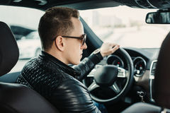 Moderner gutaussehender Mann in der Sonnenbrille, die an in seinem Luxus sitzt Lizenzfreie Stockbilder