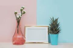 Moderner Hauptdekorspott oben mit Fotorahmen des Goldfreien raumes, Vase und tropischer Anlage auf rosa blauem Hintergrund Lizenzfreies Stockfoto