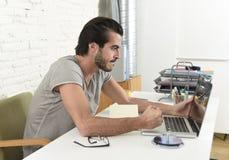 Moderner Hippie-Artstudent oder -geschäftsmann, die zu Hause im Druck mit verärgertem Umkippen des Büros des Laptops arbeiten Lizenzfreie Stockbilder