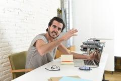 Moderner Hippie-Artstudent oder -geschäftsmann, die zu Hause im Druck mit verärgertem Umkippen des Büros des Laptops arbeiten Stockfoto