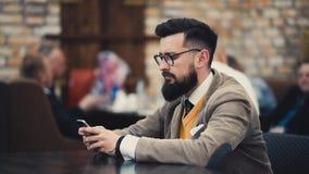 Moderner Hippie-Geschäftsmann in den Gläsern unter Verwendung des Handys stock footage
