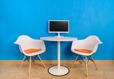 Moderner Innenbürotisch und zwei Stühle mit Computermonitor stockfotos