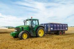 Moderner John Deere-Traktor, der blauen Anhänger zieht Stockfotografie