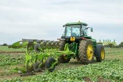 Moderner John Deere-Traktor, der einen Pflug zieht Lizenzfreie Stockfotografie