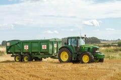 Moderner John Deere-Traktor, der grünen Anhänger zieht Stockbilder