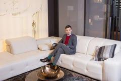 Moderner junger Mann, der auf einem Sofa sitzt Lizenzfreie Stockfotografie