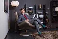 Moderner junger Mann, der auf einem Stuhl sitzt Stockfotos