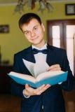Moderner junger Mann mit der Fliege, die ein Buch hält und die Kamera betrachtet Hotelzimmer im Hintergrund lizenzfreie stockfotografie