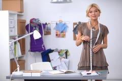 Moderner junger Modedesigner, der am Studio arbeitet stockbild