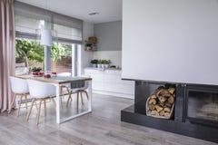 Moderner Kamin und Holz in einem geräumigen Esszimmerinnenraumesprit stockfoto