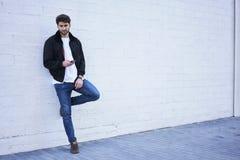 Moderner Kerl in den hellen Jeans, in einem weißen T-Shirt und in einer dunklen Jacke Stockfoto