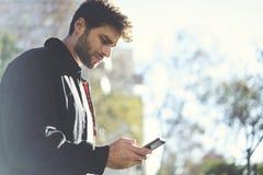 Moderner Kerl in den hellen Jeans, in einem weißen T-Shirt und in einer dunklen Jacke Lizenzfreie Stockfotos