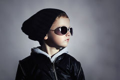 Moderner Kinderjunge in der Sonnenbrille Kind in der schwarzen Kappe Herbstart Winter Little Boy Stockfotos